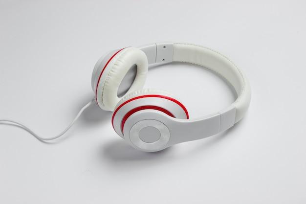 白い紙の背景に古典的な白い有線ヘッドフォン。レトロなスタイル。 80年代。ポップカルチャー。上面図。ミニマルミュージックのコンセプト