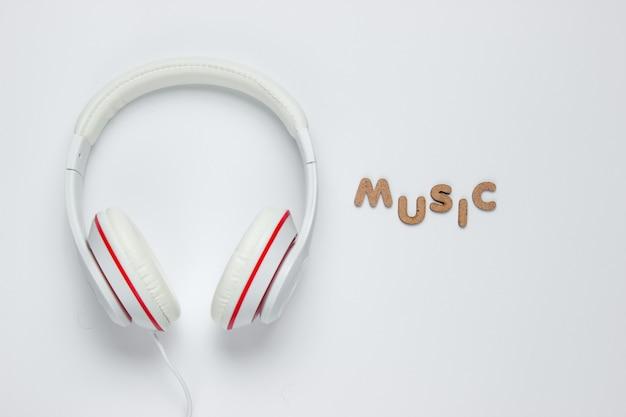 白い紙の背景に古典的な白い有線ヘッドフォン。レトロなスタイル。 80年代。ポップカルチャー。上面図。ワードミュージック