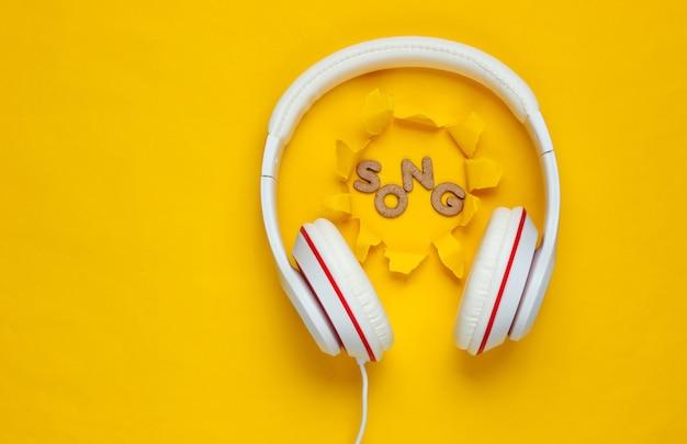引き裂かれた穴と黄色の紙の背景に古典的な白い有線ヘッドフォン。レトロなスタイル。 80年代。ポップカルチャー。上面図。