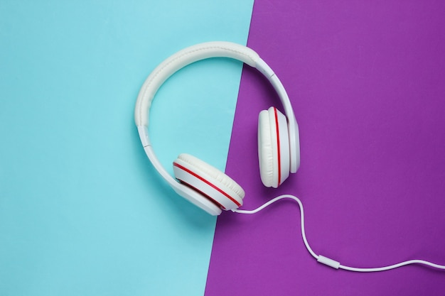 Classic white wired headphones on purple blue paper background. retro style. 80s. pop culture. top view. minimal music concept