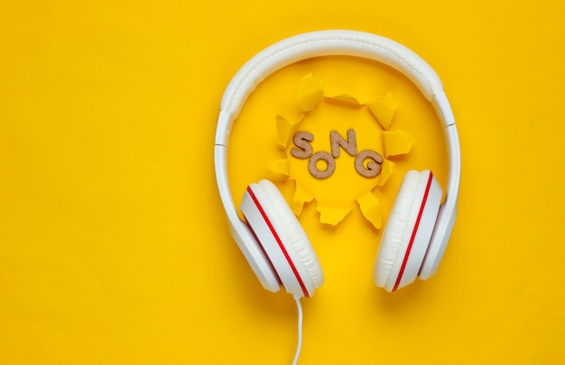 Classic white wired headphones on yellow paper background with torn hole. retro style. 80s. pop culture. top view.