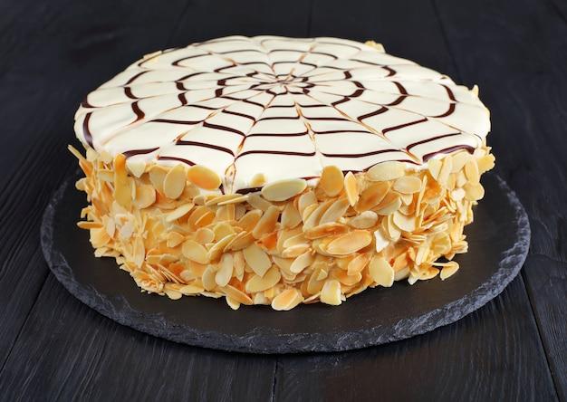 Классический цельный торт украшен кремовой глазурью из белого шоколада и паутиной из темного шоколада на черной грифельной тарелке на черном деревянном столе.