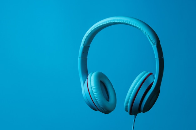 Classic wired headphones with blue neon light. retro style. minimalistic music concept.