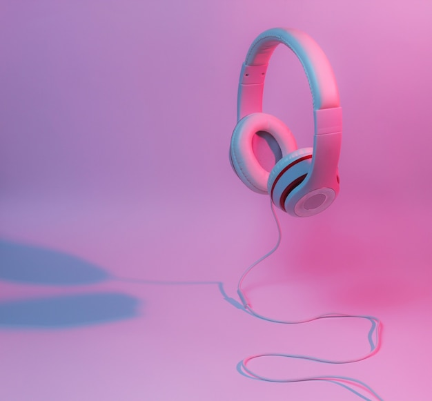 Classic wired headphones with gradient blue pink neon light. retro style. minimalistic music concept.