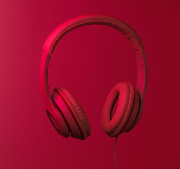 Classic wired headphones with red neon light. retro style. minimalistic music concept.