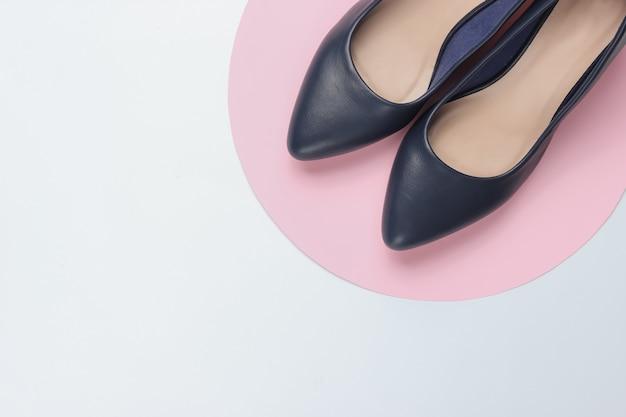 ピンクの円と白い紙の上の古典的な女性のハイヒールの靴