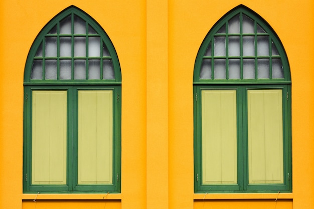 Classic wood window at yellow concrete building