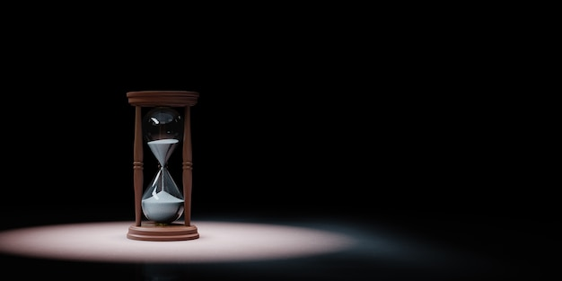 Classic wooden hourglass in the spotlight isolated