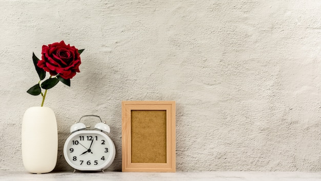 Classic wooden photo frame with alarm clock and a red rose. - blank space for message and advertising background.