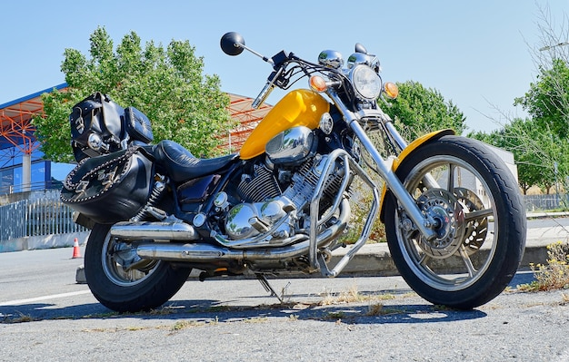 A classic yellow chopper motorcycle with black leather saddlebags parked on a road