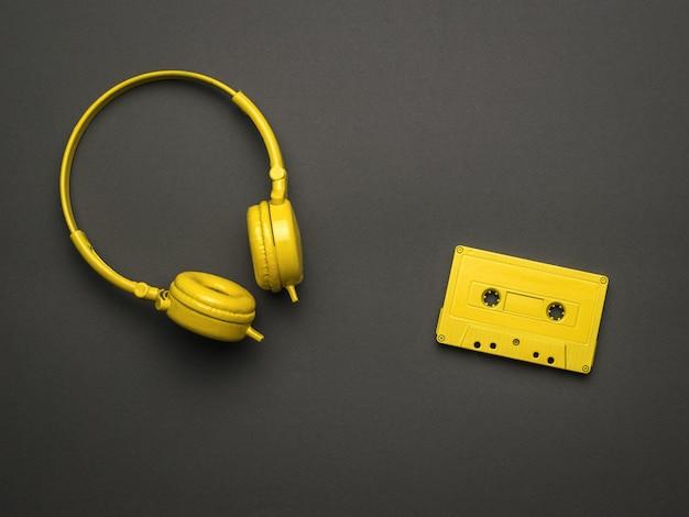 고전적인 노란색 헤드폰과 검정색 배경에 자기 테이프가 있는 노란색 카세트. 컬러 트렌드. 음악을 듣기 위한 빈티지 장비입니다. 플랫 레이.