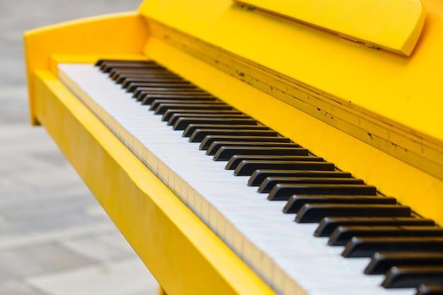 Классический желтый рояль на улице крупным планом.