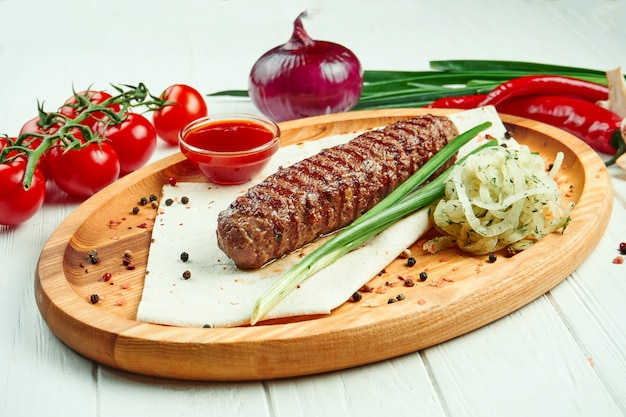 Classical arabic beef or chicken lula kebab with onion garnish on wooden board. appetising meat on the grill.