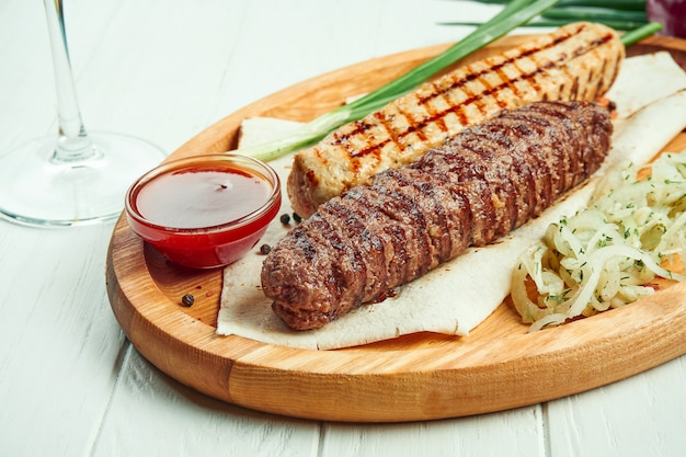 Classical arabic beef or chicken lula kebab with onion garnish on wooden board. appetizing meat on the grill