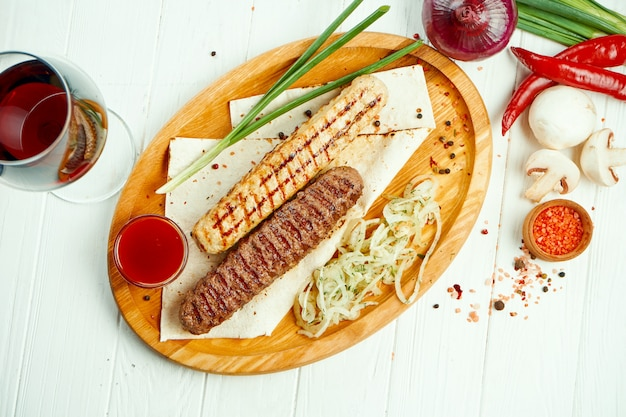 Classical arabic beef or chicken lula kebab with onion garnish on wooden board. appetizing meat on the grill.