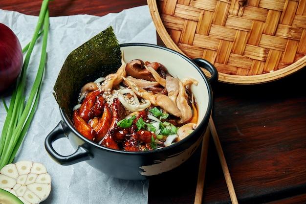 Классический азиатский суп с лапшой удон, нори, грибами шиитаке и жареной на воке курицей в черном шаре на деревянном столе с копией пространства. вид сверху, плоская кладка еды