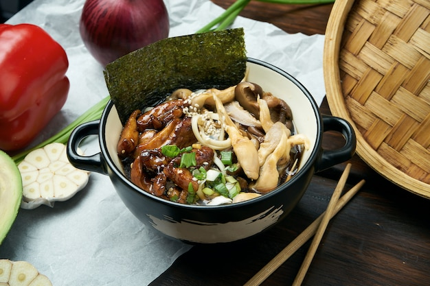 Classical asian soup with udon noodles, nori, shiitake mushrooms, and wok-fried chicken in black bowl on wooden table with copy space. top view, flat lay food