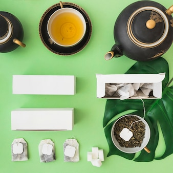 Classical asian tea set with herbal tea bag on green background