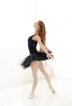 Classical ballerina woman in black dress practicing for the black swan