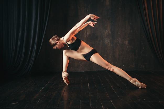 Артист классического балета в черном практике тренировки на сцене. изящная балерина позирует в студии