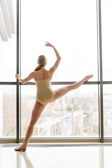Портрет артистки классического балета. красивая изящная балерина в черном на пуантах возле большого окна в светлом зале.