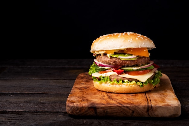 Классический бургер с помидорами, говядиной, чеддером, салатом, свежим огурцом и кетчупом на деревянном столе с копией пространства, изометрическая вертикальная ориентация