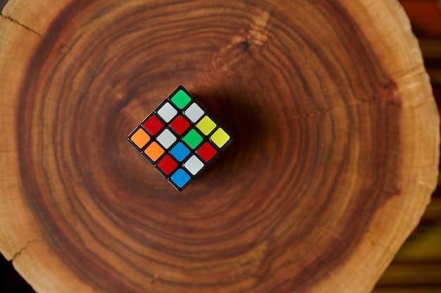 나무 그루터기에 있는 고전적인 다채로운 퍼즐 큐브, 근접 촬영 보기, 아무도. 두뇌 및 논리적 마인드 훈련, 창의적인 게임, 복잡한 문제 해결을 위한 장난감