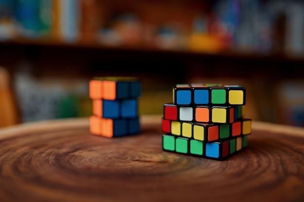 나무 그루터기에 있는 고전적인 다채로운 퍼즐 큐브, 클로즈업 보기, 아무도 없습니다. 두뇌 및 논리적 마인드 훈련, 창의적인 게임, 복잡한 문제 해결을 위한 장난감