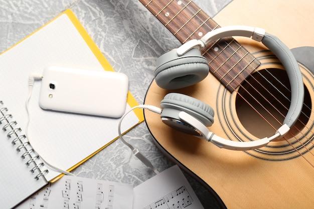 클래식 기타와 헤드폰 회색 표면에 전화