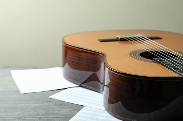 회색 질감 테이블에 클래식 기타와 악보