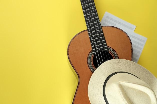 노란색 배경에 클래식 기타, 악보 및 모자