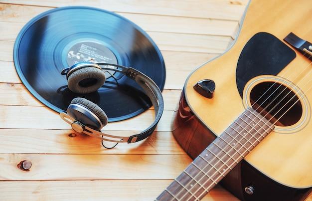 木製の背景にヘッドフォンでクラシックギター