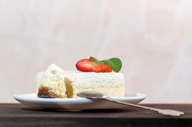 Classical new york cheesecake with slice cut out and dessert spoon