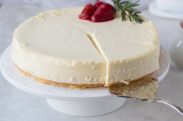 Classical new york cheesecake with strawberry sauce and rosemary