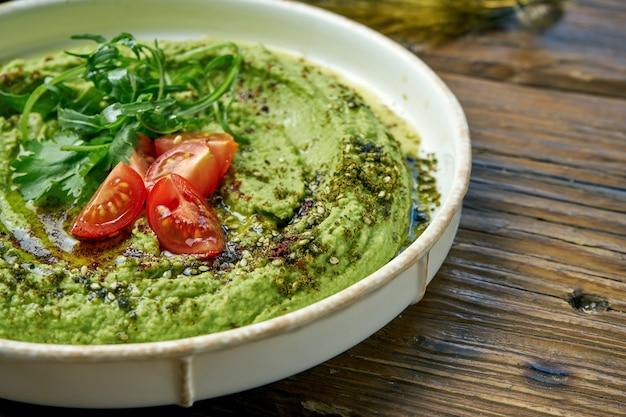 古典的な東洋の前菜-アボカドのフムスと緑とチェリートマトと木製の白いプレート