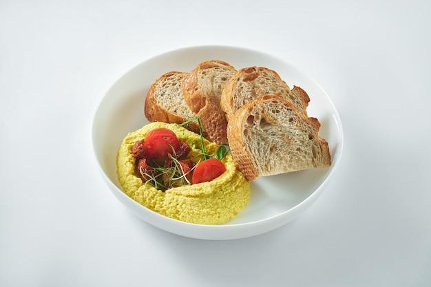古典的なオリエンタル料理-白いテーブルの上の白いプレートにクルトンと一緒に天日干しトマトとひよこ豆のフムス