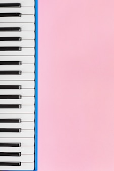 Classical piano black and white keyboard on pink background