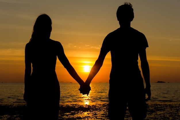 Classical valentine day scene with the silhouette of young couple holding hands while contemplating sunset at the beach.