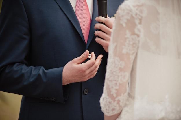 春のクラシックな結婚式。儀式。新郎は約束を言い、指輪を手に持っています。