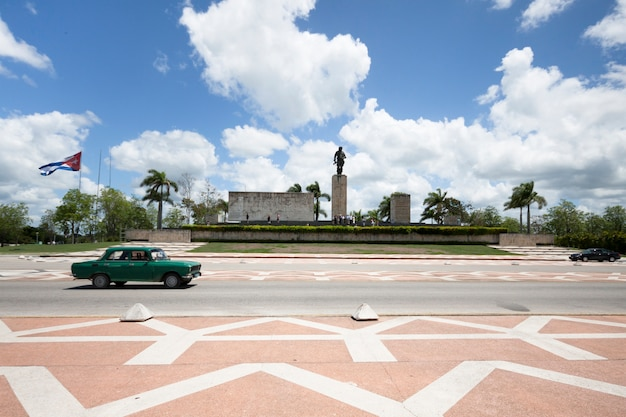 Classing car passing in front of monument in cuba