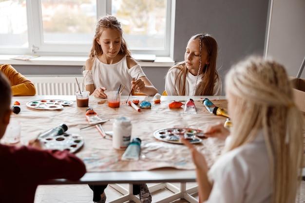 カラフルな絵の具で紙に絵を描くクラスメート