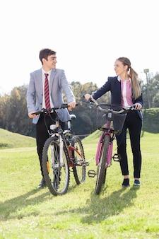 Compagni di classe parlando e sorridente accanto a loro biciclette