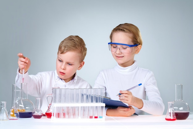 Classmates with chemical flasks and test tubes