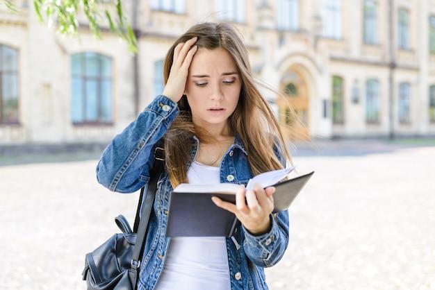 Класс сложно боится ленивый проект не готов провалить домашнее задание. крупным планом фото портрет грустной расстроенной плачущей испуганной испуганной испуганной депрессивной девушки, смотрящей на книгу в руке, касающейся головы