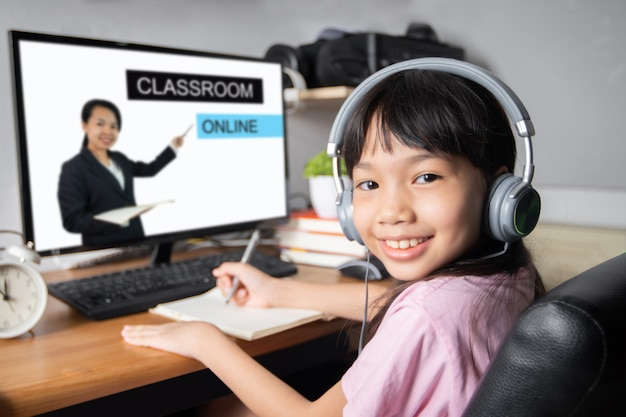 Classroom and education online and school network, youth asian or thai girl student learning on desktop computer at home teacher teaching as  digital digital tv during coronavirus or covid 19 disease