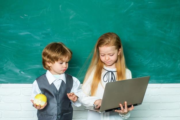 教室の最初の学校の日の先生の女子高生は、学校の教室で子供たちの宿題を手伝っています...