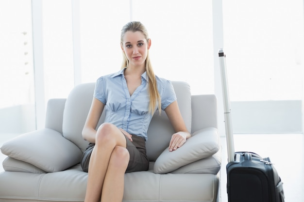 Classy blonde businesswoman waiting sitting on couch next to her suitcase