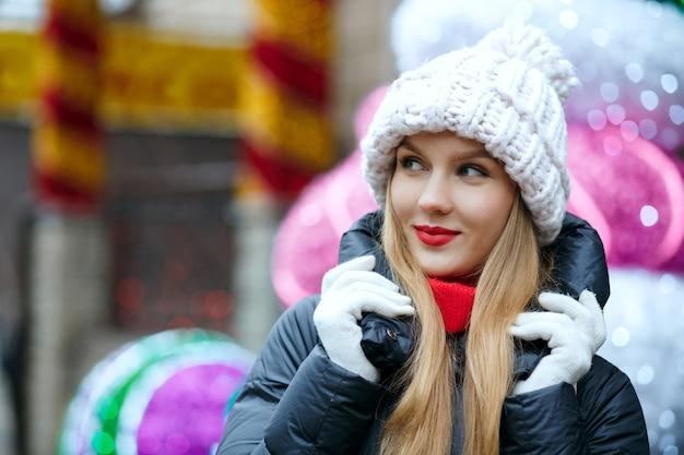 花輪の背景の上の通りで冬の休日を楽しんでいる赤い唇を持つ上品な金髪モデル