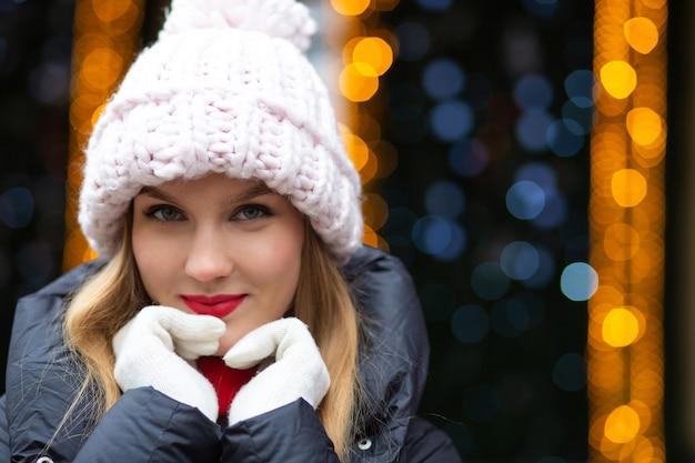 ボケと花輪の背景の上の通りでポーズをとってニット帽をかぶった赤い口紅を持つ上品なブロンドの女性