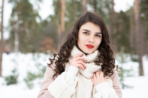 長い髪の上品なブルネットの女性は冬にコートを着ています。テキスト用のスペース